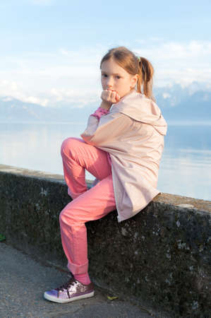 one child: Cute little girl resting by the lake, wearing pink coat and trousers