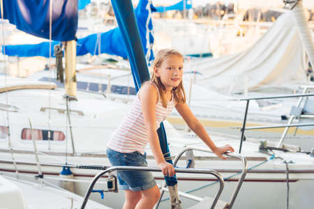 Cute little girl resting on a yacht in a port on a nice summer day Stock Photo