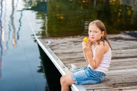 comiendo helado: Retrato al aire libre de una niña linda, comiendo helado, situada junto al lago
