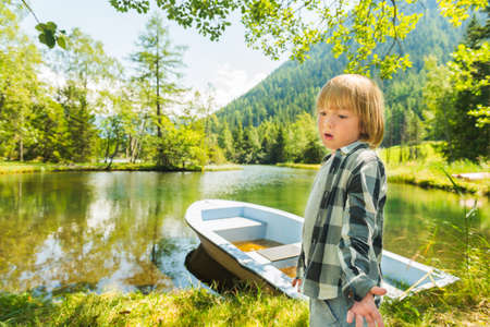 lac: Cute little boy hiking in swiss Alps, resting by the lake Stock Photo