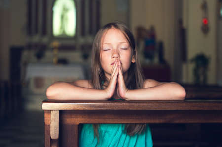 Child praying in church Foto de archivo