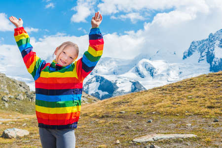 arms wide open: Cute little girl with arms wide open, wearing colorful coat, standing in front of Gornergrat glacier, Switzerland Stock Photo