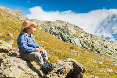 knitted jacket: Cute kid boy resting in Alps, wearing warm knitted jacket and mountain boots