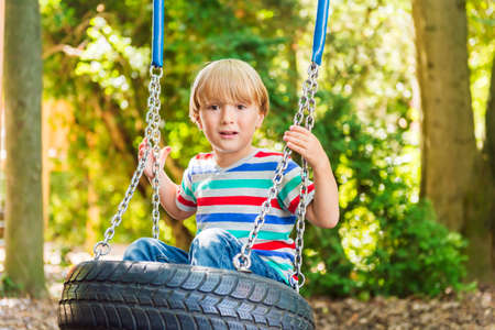 stipe: Cute young blond boy having fun on a swing on a nice summer day, wearing stipe tee