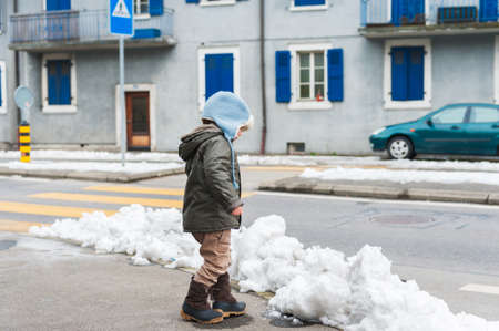boots: Cute little toddler boy playing with the snow outdoors, walking by the road, wearing warm jacket and boots Stock Photo