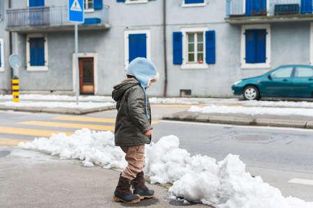 botas: Peque�o muchacho lindo del ni�o que juega con la nieve al aire libre, caminando por la carretera, el uso de chaqueta y botas