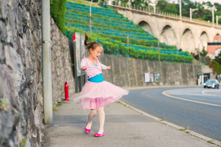 street love: Outdoor portrait of a cute little girl of 7 years old, walking to dance school and dancing in the street, wearing purple ballet dress Stock Photo