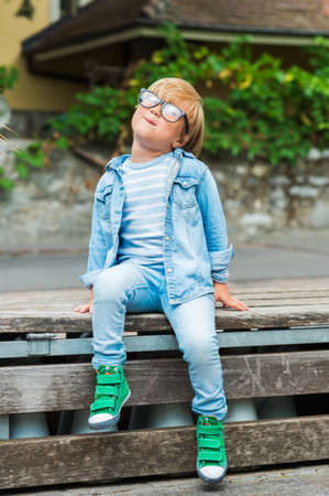 blonde boy: Outdoor portrait of a cute little boy in glasses, wearing denim clothes and green shoes