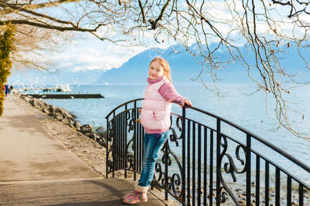 young schoolgirl: Outdoor portrait of adorable little girl wearing pink jacket and warm boots