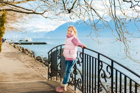 happy young: Retrato al aire libre de la ni�a adorable vistiendo chaqueta rosa y botas calientes