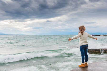 Cute little girl of 8 years old playing by the lake on a very windy day, wearing warm white knitted pullover, arms wide open, back view