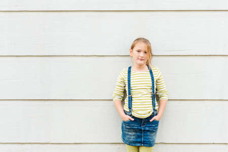 denim skirt: Outdoor portrait of a cute little girl wearing green t-shirt and denim skirt