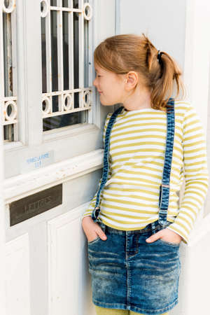 denim skirt: Outdoor portrait of a cute little girl,  peeking through the door window, wearing stripe top and denim skirt with suspenders
