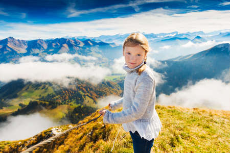 Portrait of a cute little girl in mountains, wearing grey pullover, Moleson-sur-Gruyeres, canton of Fribourg, Switzerland Archivio Fotografico