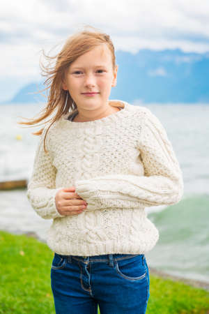 Cute little girl of 8 years old playing by the lake on a very windy day, wearing warm white knitted pullover