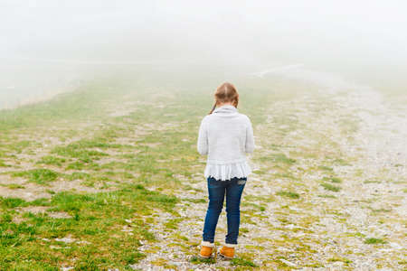 8 years old: Cute little girl of 8 years old playing outdoors on a very foggy day, wearing grey warm pullover, back view Stock Photo