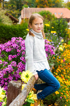 8 years old: Outdoor portrait of a cute little girl of 8 years old, sitting on a fence