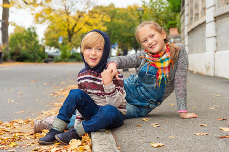 pullovers: Autumn portrait of 2 adorable kids in a city, wearing warm pullovers and denim jeans Stock Photo