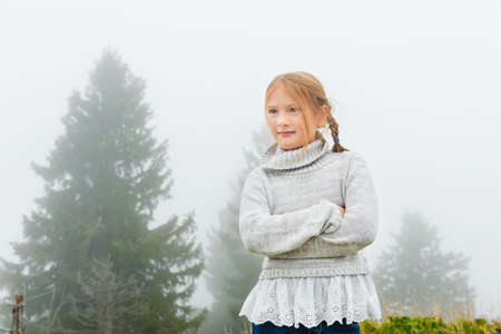 8 years: Cute little girl of 8 years old playing outdoors on a very foggy day, wearing grey warm pullover