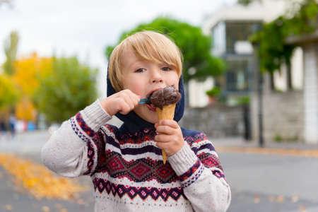 stylish boy: Cute little boy eating chocolate ice cream outdoors