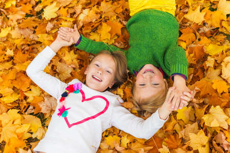 Adorable little kids playing in autumn park, laying on bright yellow and orange leaves