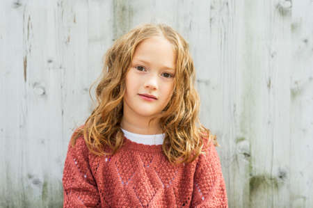 pullover: Close up portrait of a cute little girl of 8 years old with curly hair, wearing terracotts pullover, sitting against grey wooden background