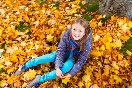 8 years: Autumn portrait of a cute little girl of 8 years old, playing with yellow leaves in the park Stock Photo