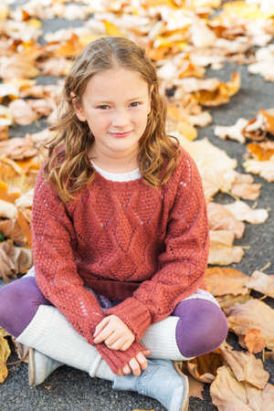 leg warmers: Autumn portrait of a cute little girl with curly hair, wearing terracota pullover, leg warmers and blue boots