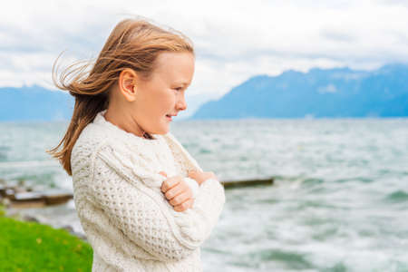 very windy: Cute little girl of 8 years old playing by the lake on a very windy day, wearing warm white knitted pullover