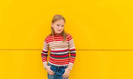 denim skirt: Portrait of a cute little girl of 8 years old, wearing stripe roll neck pullover and denim skirt, standing next to bright yellow wall
