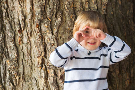 4 year old: Little 4 year old blond caucasian boy in front of an old and massive tree pretending to take a picture with his hands