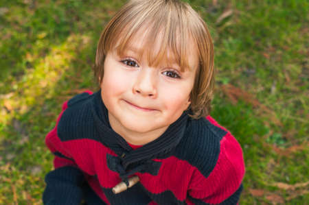 little people: Outdoor close up portrait of adorable little blond boy of 4 years old with hairstyle and sweet smile on his face