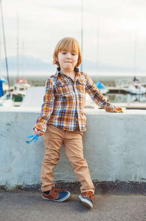 4 years old: Outdoor portrait of a cute fashion little boy of 4 years old, wearing yellow plaid shirt, beige trousers and sneakers Stock Photo