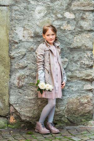 Openlucht portret van een leuk meisje met witte rozen, het dragen van beige jas en roze jurk