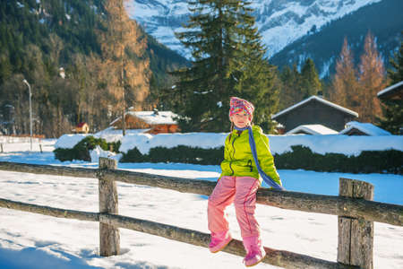 warm jacket: Cute little girl playing outdoors in winter time, sitting on the fence, wearing warm jacket and pants