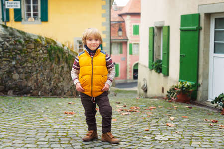 45 years old: Outdoor portrait of a cute little boy of 4-5 years old, wearing warm yellow vest Stock Photo