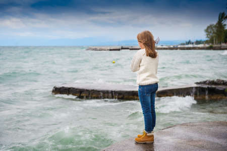 very windy: Cute little girl of 8 years old playing by the lake on a very windy day; wearing warm white knitted pullover; denim jeans and boots Stock Photo