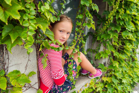 red cardigan: Outdoor portrait of a cute young girl sitting on the window sill with ivy, wearing colorful skirt, red and white stripe cardigan and pink laceless shoes