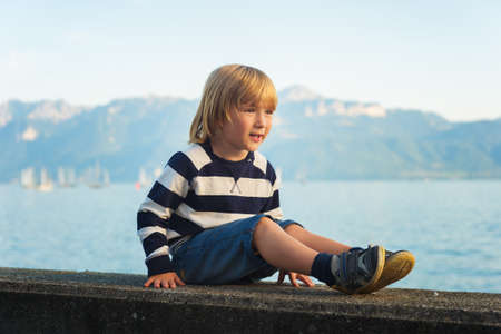 boy shorts: Portrait of beautiful smiling cute little boy. 3-4 years old little child playing outside by the lake Geneva, in summer or spring. Boy sitting alone by the lakeside at sunset, wearing stripe jersey sweatshirt and denim shorts