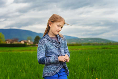 knitted jacket: Fashion portrait of cute little girl of 7 years old, wearing blue trousers and knitted jacket