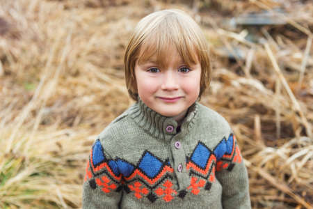 45 years old: Outdoor close up portrait of a cute little boy of 4-5 years old, playing by the lake on a cold day