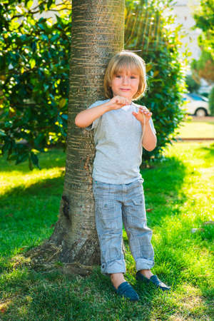 moccasins: Outdoor fashion portrait of a young cute little blond boy Stock Photo