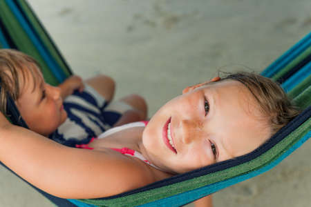 preteen model: Adorable kids resting in a hammock on the beach