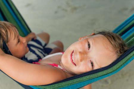 little model: Adorable kids resting in a hammock on the beach