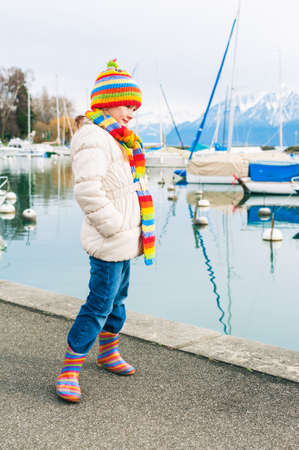 warm jacket: Adorable little girl plying by the lake in early spring, wearing white warm jacket, colorful set of scarf and hat and rain boots, vertical image