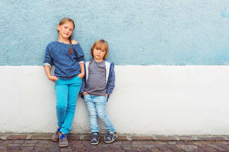 Two kids, girl and little boy, posing outdoors, standing against blue wall