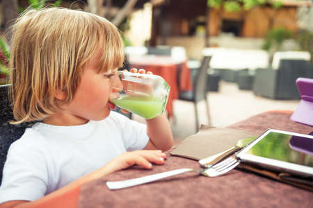 cute attitude: Adorable little boy drinking fresh apple juice in a restaurant Stock Photo