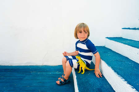swim shoes: Adorable little boy playing with a dinosaur toy, wearing funny swim suit and beach shoes, sitting on blue stairs, summer vacations concept