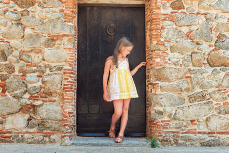 little girl posing: Outdoor fashion portrait of a cute little girl wearing yellow dress