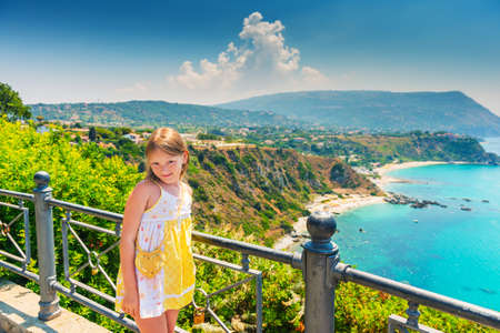 capo: Adorable little girl posing against amazing view of Capo Vaticano, Calabria, Italy